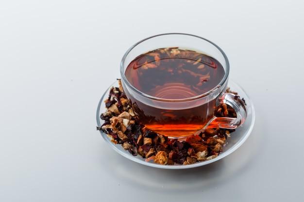 Parzona herbata w filiżance z suszonymi ziołami i owocami