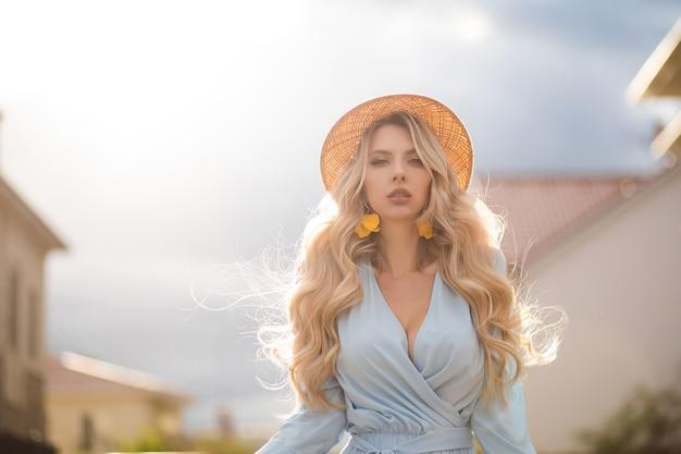 Pas całkiem młoda kobieta ubrana w letnią sukienkę i słomkowy kapelusz podczas spaceru po ulicy miasta. koncepcja piękna i mody
