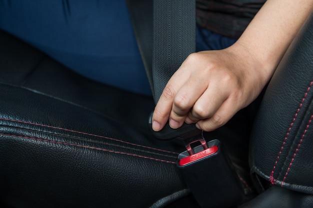 Pas samochodowy. kobieta zapina pas bezpieczeństwa w samochodzie bezpieczna jazda. pas bezpieczeństwa w ręku.