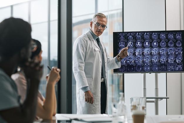 Pas w górę portret dojrzałego lekarza przedstawiającego prezentację na konferencji medycznej i wskazującego na zdjęcia rentgenowskie, kopia przestrzeń