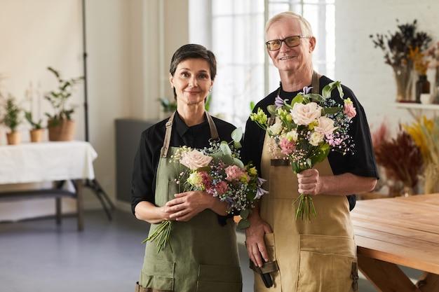 Pas w górę portret dojrzałej pary trzymającej kwiaty w kwiaciarni i patrzącej na kamerę