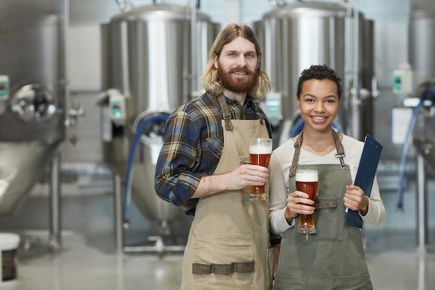 Pas w górę portret dwóch uśmiechniętych młodych pracowników trzymających szklanki piwa i patrzących na kamerę stojąc w warsztacie w fabryce browarnictwa, kopia przestrzeń
