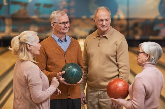 Pas w górę portret grupy starszych ludzi trzymających kule do kręgli i rozmawiających, ciesząc się aktywną rozrywką w kręgielni, kopia przestrzeń