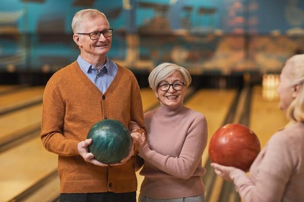 Pas w górę portret grupy szczęśliwych starszych ludzi trzymających kule do kręgli i rozmawiających, ciesząc się aktywną rozrywką w kręgielni, kopia przestrzeń