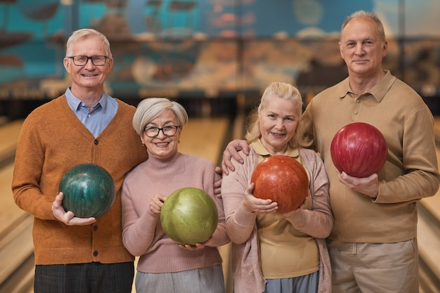 Pas w górę portret grupy szczęśliwych starszych ludzi trzymających kule do kręgli i uśmiechających się do kamery, jednocześnie ciesząc się aktywną rozrywką w kręgielni, kopia przestrzeń