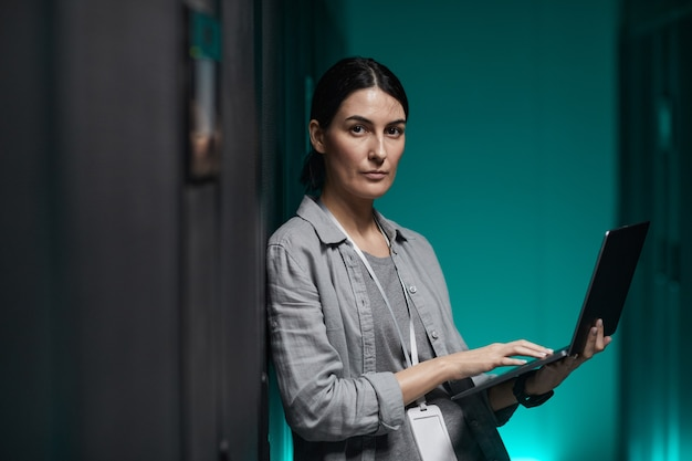 Pas w górę portret kobiety inżynier danych trzymającej laptopa i patrzącej na kamerę podczas pracy z superkomputerem w serwerowni, kopia przestrzeń
