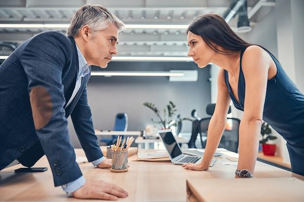 Pas w górę portret ludzi biznesu, stojąc przy biurku z drewna i patrząc na siebie