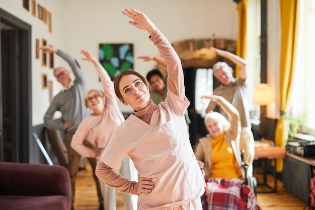 Pas w górę portret młodej kobiety koordynującej grupę starszych ludzi cieszących się porannymi ćwiczeniami w reti...