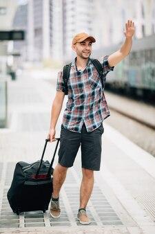 Pas w górę portret przystojnego mężczyzny podnoszącego rękę odwracając się i uśmiechając się na dworcu kolejowym