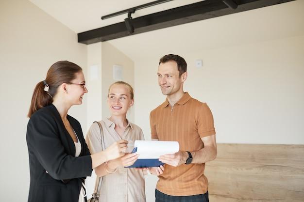 Pas w górę portret szczęśliwej pary podpisującej umowę z agentem nieruchomości podczas wycieczki po mieszkaniu w nowym domu, kopia przestrzeń