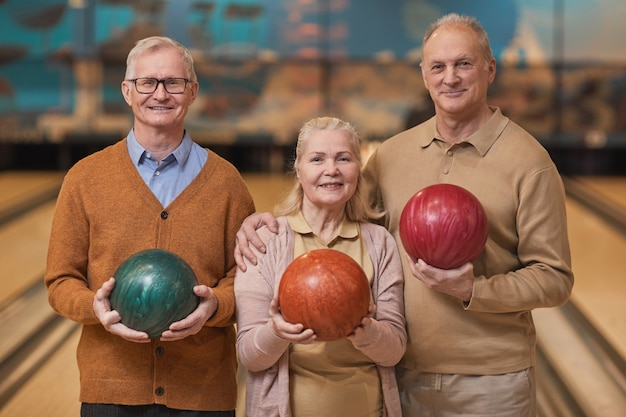 Pas w górę portret trzech uśmiechniętych starszych ludzi trzymających kule do kręgli i patrzących w kamerę podczas aktywnej rozrywki w kręgielni, kopia przestrzeń
