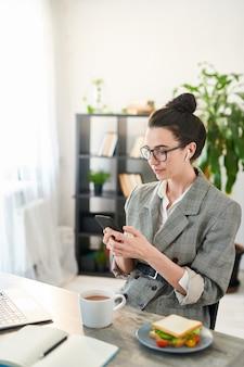 Pasa w górę portret młodej bizneswoman za pomocą smartfona w miejscu pracy i uśmiechnięta, kopia przestrzeń