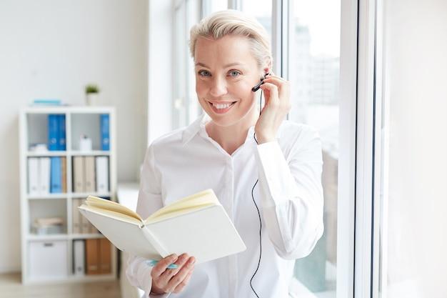 Pasa w górę portret uśmiechnięta bizneswoman noszenie zestawu słuchawkowego i patrząc podczas pracy w call center