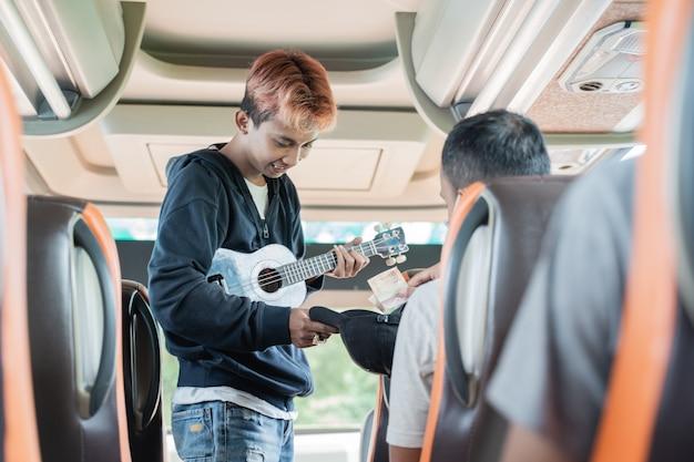 Pasażer daje pieniądze ulicznemu ulicznemu noszącemu ukulele w autobusie