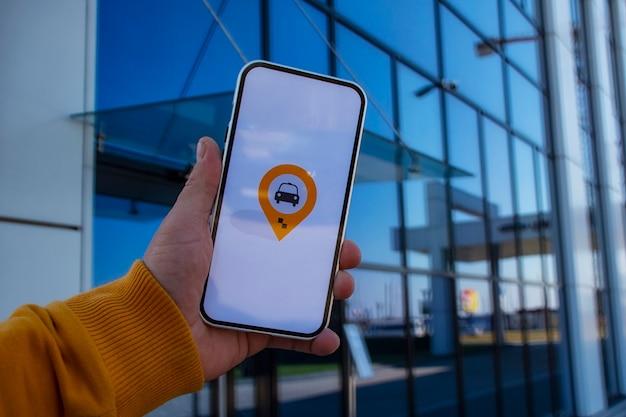 Pasażer na parkingu trzyma smartfon z aplikacją mobilną i dzwoni po taksówkę online.