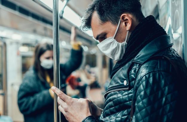 Pasażer w masce ochronnej czytający wiadomość na swoim smartfonie