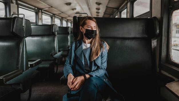 Pasażer w pociągu siedzi i ma na sobie maskę medyczną