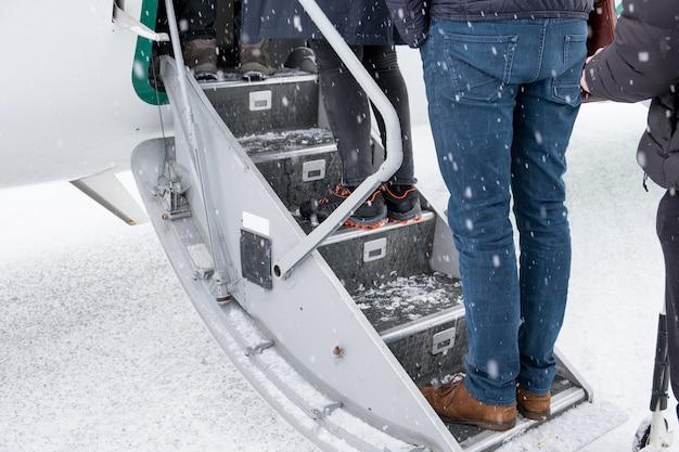 Pasażerowie czekający na pokład samolotu w śnieżny dzień
