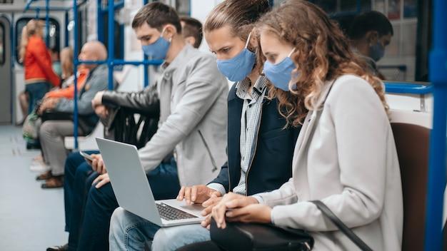 Pasażerowie metra noszący maski ochronne korzystający z laptopów