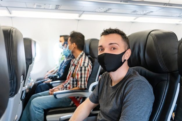 Pasażerowie samolotów mają na twarzach maski medyczne. podróże lotnicze podczas pandemii koronawirusa. wymagania linii lotniczych.