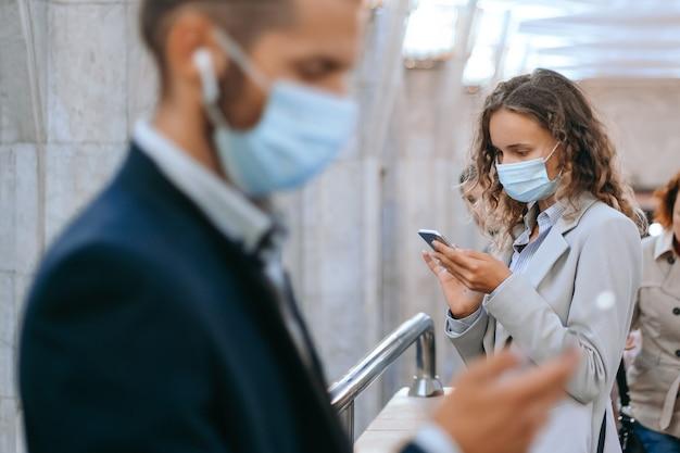 Pasażerowie w maskach ochronnych na przejściu metra