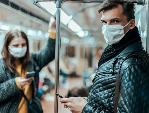 Pasażerowie w maskach ochronnych stoją w wagonie metra. koronawirus w mieście
