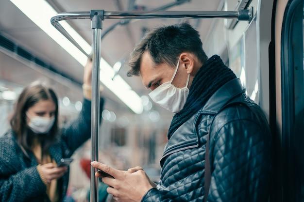 Pasażerowie w maskach ochronnych stoją w wagonie metra