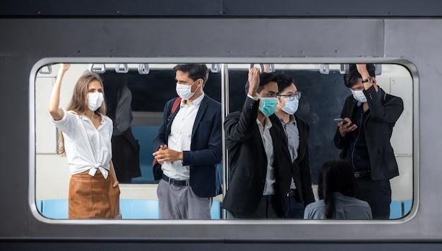 Pasażerowie w masowym szybkim pociągu tranzytowym, pasażerowie w tłumie wewnątrz pociągu, pasażerowie stojący w pociągu skytrain, transport systemu komunikacji masowej w bangkoku.