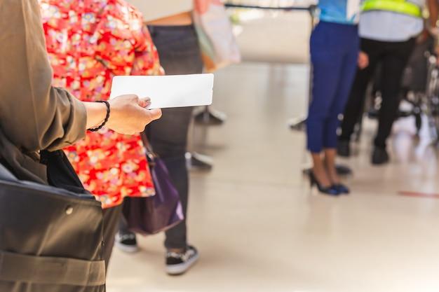 Pasażerowie z ręką trzymającą kartę pokładową w kolejce do odlotu.