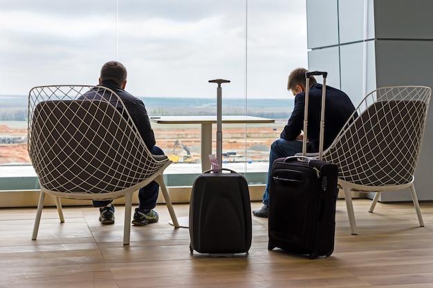 Pasażerowie z walizkami czekają na odlot w części wypoczynkowej na lotnisku