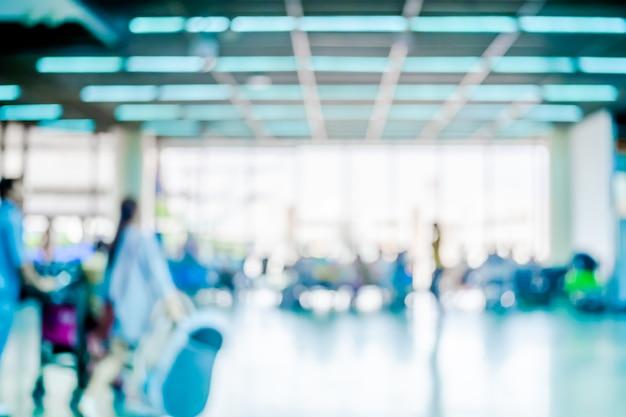Pasażerski czekanie dla lota przy lotniskowym terminal zamazuje tło