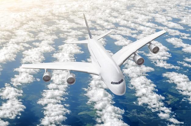 Pasażerski ogromny liniowiec w locie nad chmurami i błękitnym niebem.