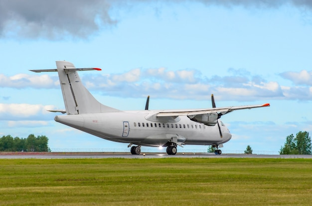 Pasażerski samolot turbośmigłowy lądujący na pasie startowym na tle błękitnego nieba.