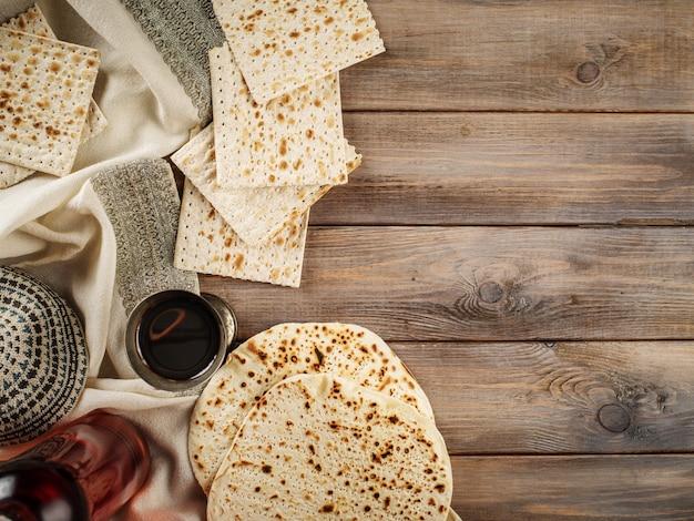 Pascha matzoh żydowski chleb świąteczny i koszerne wino na tle drewnianego stołu.
