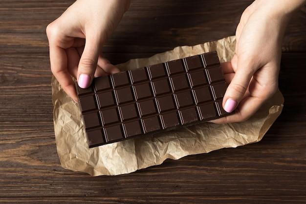 Pasek czarnej gorzkiej czekolady na drewniane brązowe tło widok z góry