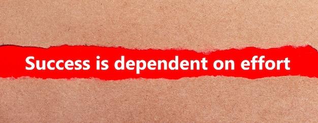 Pasek czerwonego papieru pod podartym brązowym papierem. białe litery na czerwonym papierze sukces zależy od wysiłku.