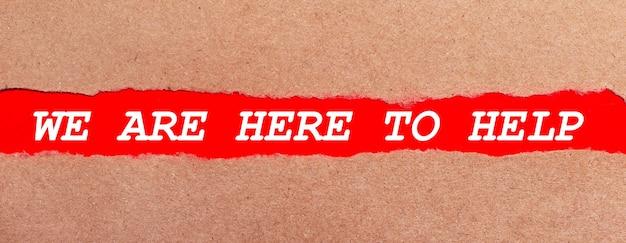 Pasek czerwonego papieru pod rozdartym brązowym papierem. białe litery na czerwonym papierze jesteśmy tu pomoc. widok z góry
