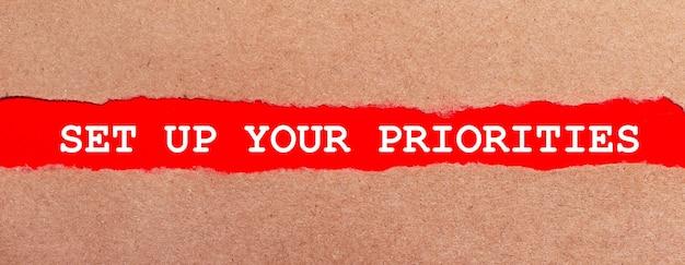 Pasek czerwonego papieru pod rozdartym brązowym papierem. białe litery na czerwonym papierze ustal swoje priorytety. widok z góry