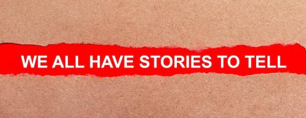 Pasek czerwonego papieru pod rozdartym brązowym papierem. białe litery na czerwonym papierze wszyscy mamy historie do opowiedzenia. widok z góry