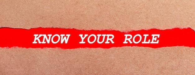 Pasek czerwonego papieru pod rozdartym brązowym papierem. biały napis na czerwonym papierze poznaj swoją rolę. widok z góry