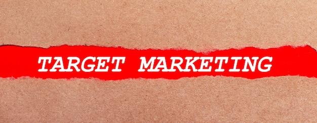 Pasek czerwonego papieru pod rozdartym brązowym papierem. biały napis na czerwonym papierze target marketing. widok z góry