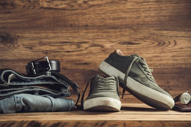 Pasek do dżinsów z butami sportowymi z zegarkiem na drewnianym stole