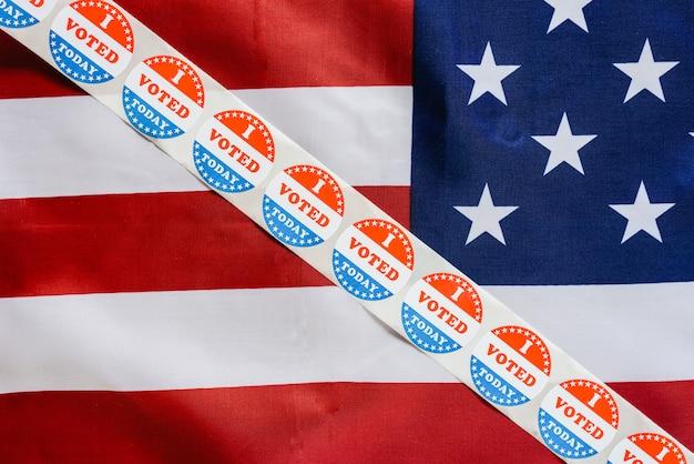 Pasek naklejek głosuję dziś nad flagą usa po głosowaniu w urnie wyborczej.
