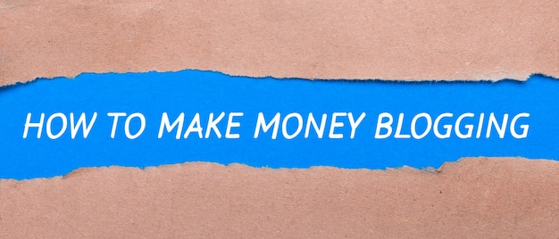 Pasek niebieskiego papieru z napisem jak zarabiać blogowanie pomiędzy brązowym papierem. widok z góry