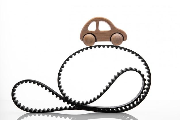 Pasek rozrządu z zabawkarskim samochodem na białej ścianie