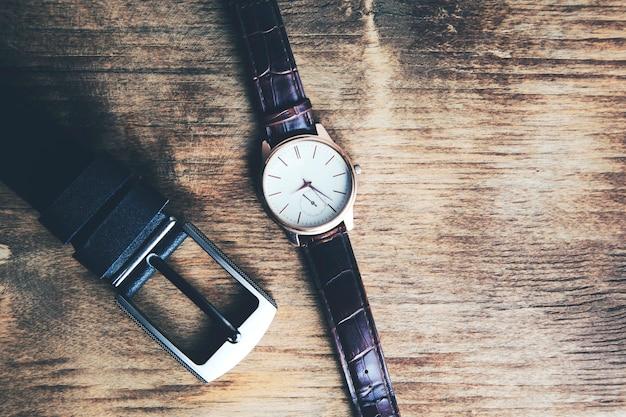 Pasek z zegarkiem na tle drewnianego stołu