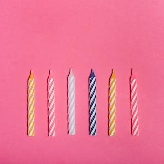 Pasiaste kolorowe świeczki na różowym tle