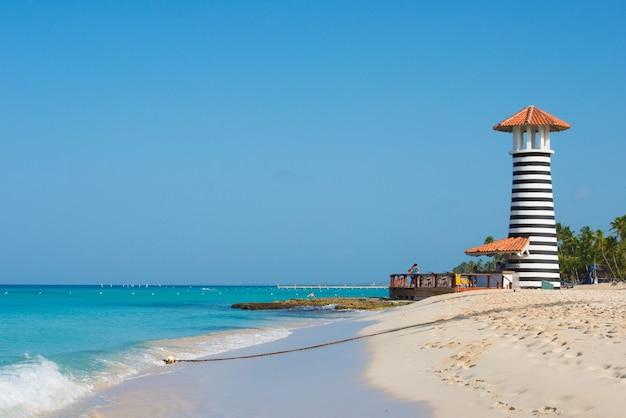 Pasiasty czerwono biały latarnia morska na wybrzeżu morza karaibskiego. republika dominikany.
