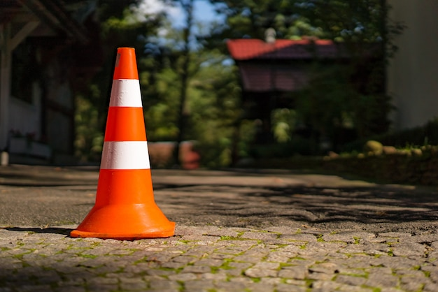 Pasiasty plastikowy drogowy znak dla parkować na bruku na zamazanym tle.