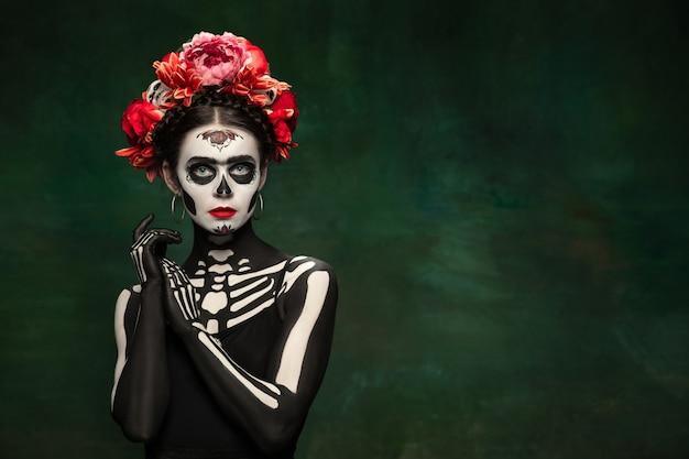 Pasjonat. młoda dziewczyna jak śmierć santa muerte saint lub sugar skull z jasnym makijażem. portret na białym tle na ciemnozielonym tle studio z lato. świętowanie halloween lub dnia zmarłych.